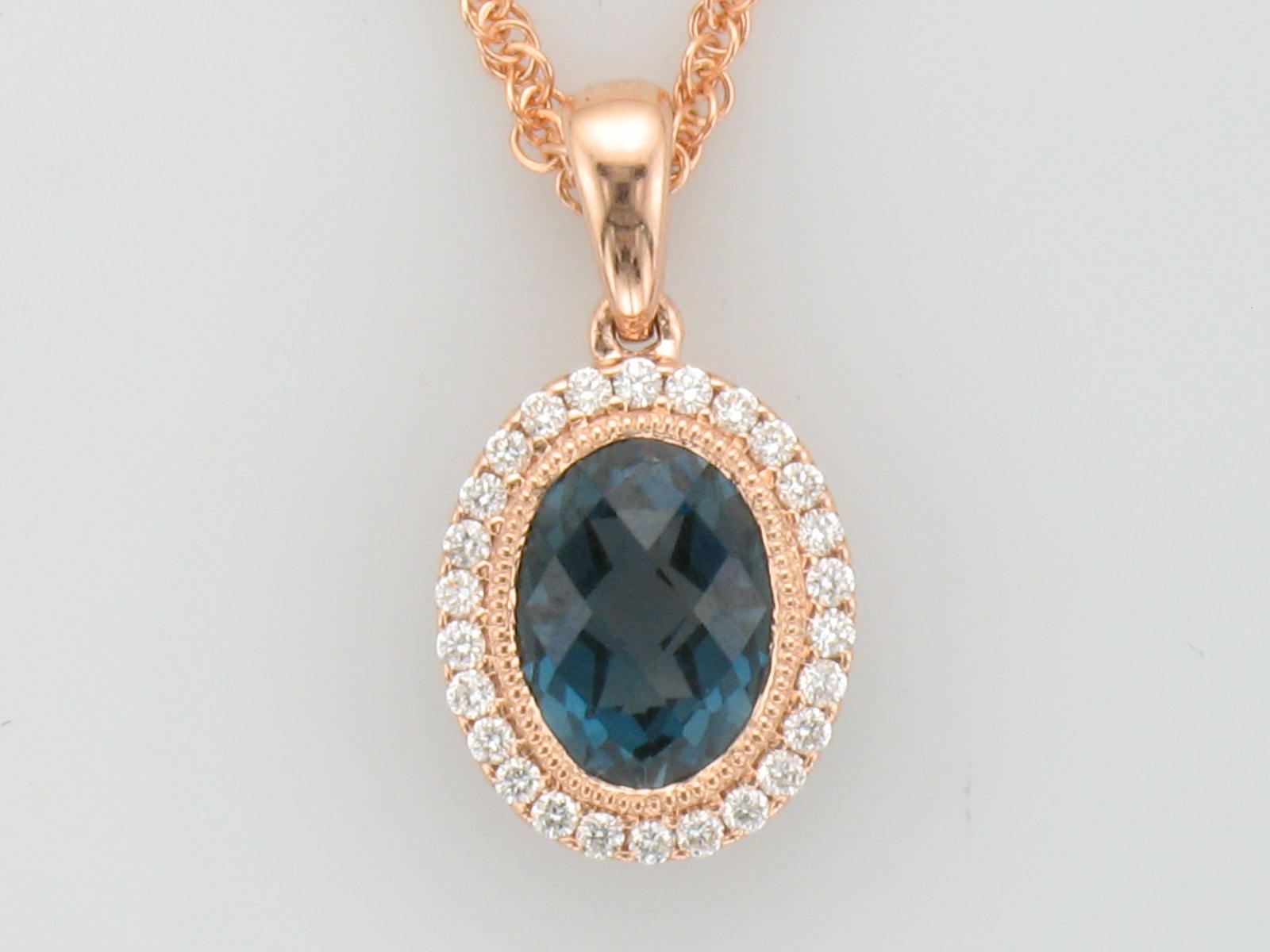 close view Rose gold Pendant with London Blue Topaz Oval with a Halo of Diamonds and Vintage Accent