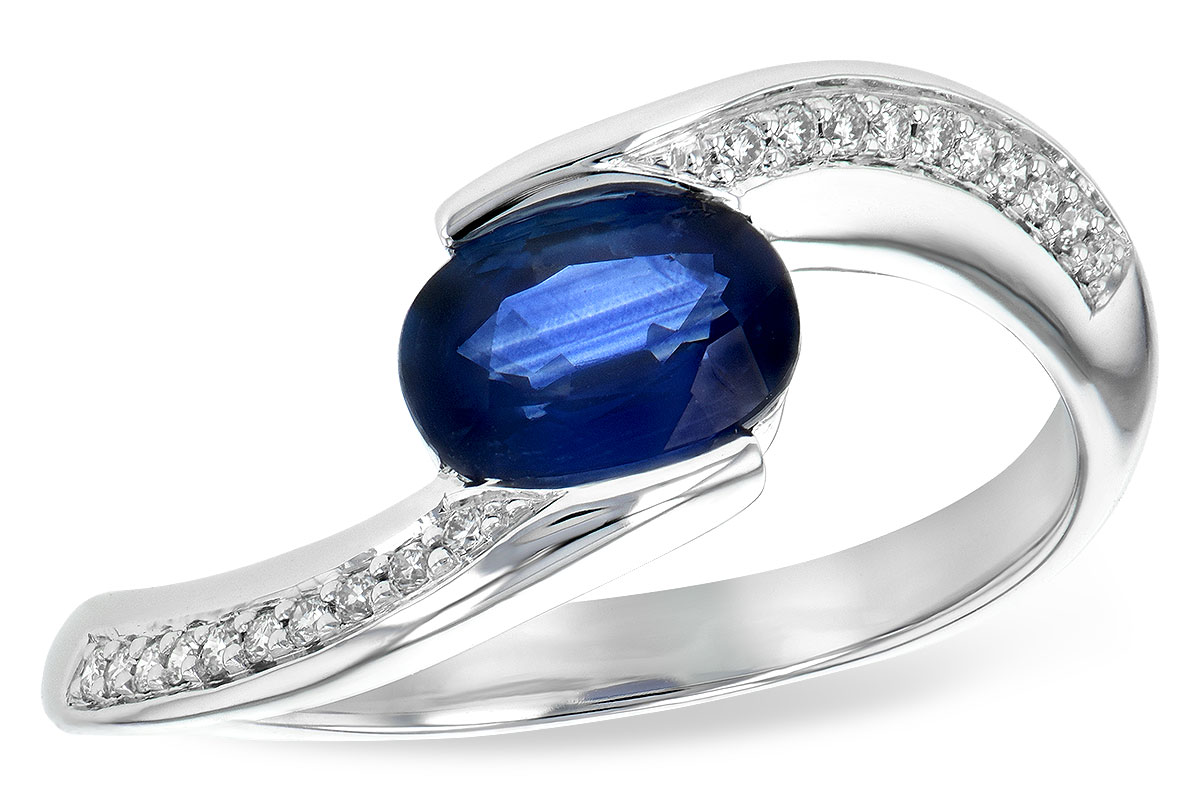 Oval .90ct sapphire set at an angle with split shank of 14k white gold with round accenting G SI1/SI2 diamonds set down the band totaling .08ct