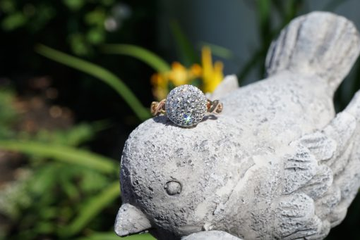 Round diamond cluster ring with .70ct GH SI2 diamonds set into the center of 14k white gold and braided style 14k rose gold band