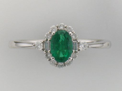 Oval Emerald Ring surrounded by 8 round accenting diamonds and 2 emerald cut diamonds and one round diamond on each side of shank-all 14k white gold diamonds totaling .20ct