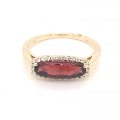 Oblong Garnet vintage style ring with checkerboard 1.60ct Mozambique Garnet surrounded by round accenting diamonds totaling .11ct, 14k yellow gold