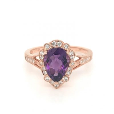 Sugar Plum Shimmer 1.53ct Pear Shape amethyst ring with round accenting diamonds framing the center gem and continuing down the sides of the ring millgrain settings surrounding the amethyst, diamonds totaling .22ct, 14k rose gold