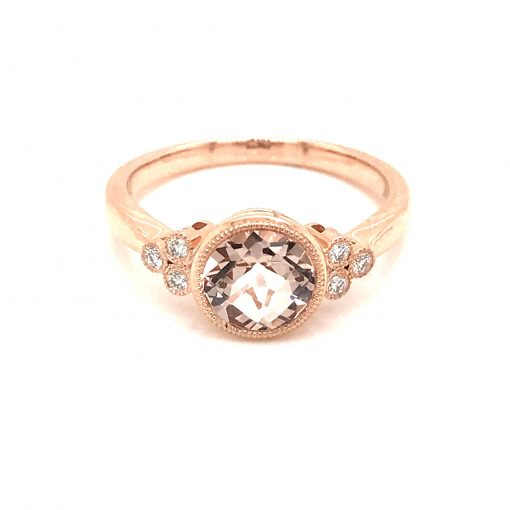 Round 1ct Morganite ring bezel set in the center with milgrain edging around the bezel and three round accenting diamonds set on each side of center, all bezel set with Milgrain, 14k rose gold, diamonds totaling .07ct