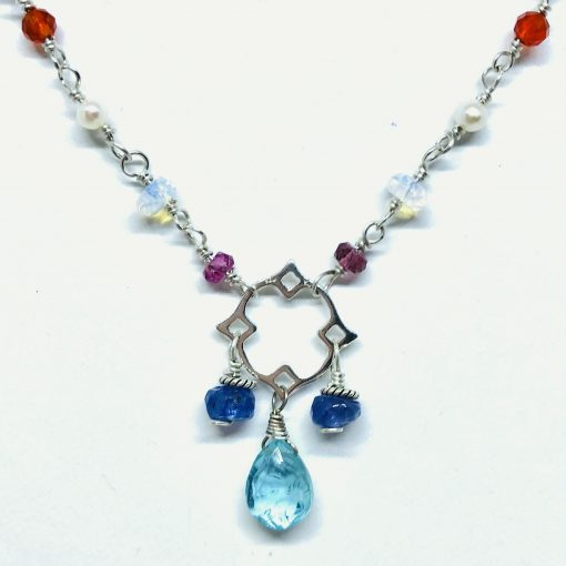 Multi Color necklace with 3mm Pink Tourmaline, 4mm faceted moonstone, 3.5-4mm faceted Blue Topaz bead, 2mm round white freshwater pearl and 3mm Round Carnelian beads all set up the chain and in the center a Apatite Briolette and two 5mm faceted Tanzanite roundel bead, adjustable length from 17-18 inches, sterling silver