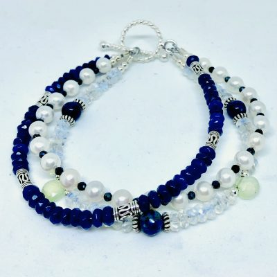 Triple strand bracelet with freshwater pearls, three 6mm Lapis, dyed blue jade, moonstone and 2 Peanite Briolette with mini accenting blue spinel. Sterling silver accents with twisted silver toggle clasp