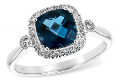Cushion Cut London Blue Topaz ring with a halo of round brilliant cut accenting diamonds surrounding the blue topaz. On each side of the diamond halo there is one round accenting diamond bezel set with a beaded milgrain border. The total diamond weight is .16 carat, G Color, SI1/2 clarity.