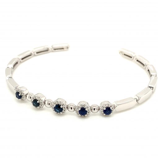 Cuff bangle style bracelet with 5 round blue sapphires each surrounded by a halo of accenting diamonds, diamonds totaling .63ct, 14k white gold