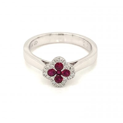 Ring with 5 round rubies set into clover shape lined with round accenting diamonds surrounding the clover, diamonds totaling .10ct, 14k white gold