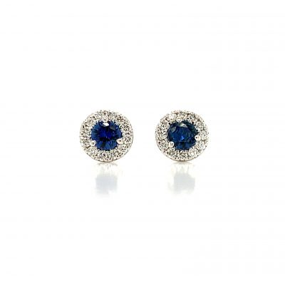 Round sapphire post earrings with round accenting diamonds surrounding the sapphire, all diamonds totaling .19ct, all 14k white gold