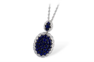 Oval pendant with accenting blue sapphires set in center surroudned by round accenting diamonds, sapphires totaling 1.23ct and diamonds totaling .36ct. 18 inch white gold chain, 14k white gold